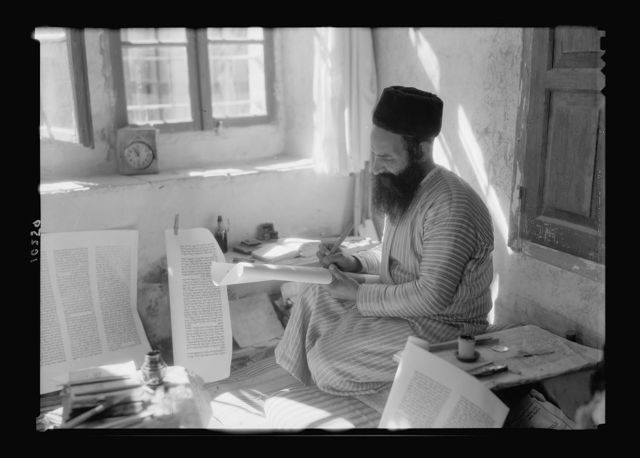 Orthodox Jewish scribe writing the Torah on parchment