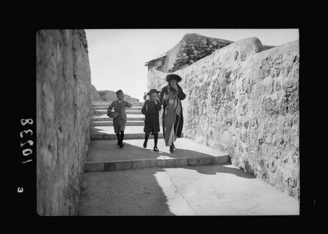 Orthodox Jews on their usual Sabbath walk to the Wailing Wall (1 man 2 youths covering f[aces] with hands)