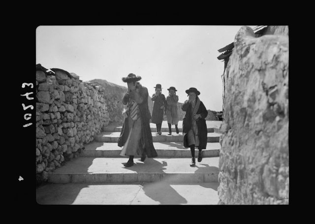 Orthodox Jews on their usual Sabbath walk to the Wailing Wall (1 man, 3 youths, covering face)