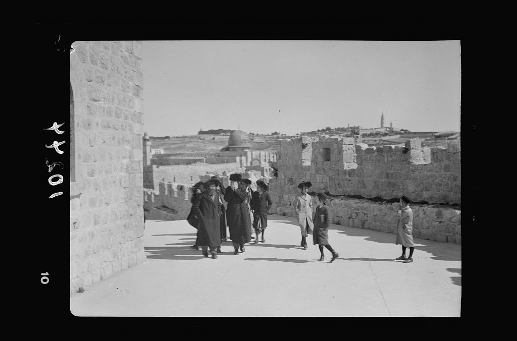 Orthodox Jews on their usual Sabbath walk to the Wailing Wall (group of men & youths, Mt. Oliv[et] in backg[round])