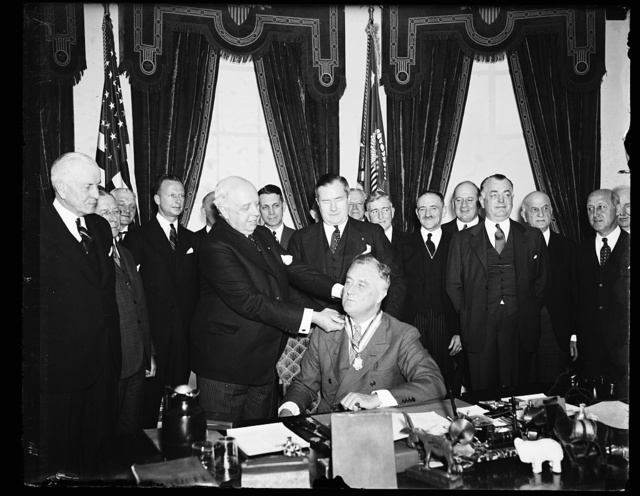PAN AMERICA SOCIETY HEAD GIVES MEDAL TO ROOSEVELT. JOHN L. MERRILL, PRESIDENT OF THE PAN AMERICAN SOCIETY, PLACES THE SOCIETY'S AWARD ABOUT THE NECK OF PRESIDENT ROOSEVELT. SPRUILLE BRANDEN, MEMBER OF THE SOCIETY'S COUNCIL, IS DIRECTLY BEHIND THE PRESIDENT. THE AWARD WAS FOR ROOSEVELT'S POLICY PROMOTING FRIENDSHIP BETWEEN THE NATIONS OF THE WESTERN HEMISPHERE