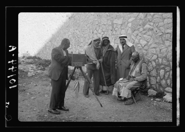 Peasants being photographed for identity cards, headdress removed