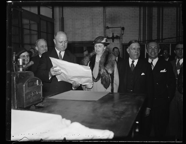 POSTMASTER GENERAL JAMES A. FARLEY AND MRS. ROOSEVELT, INSPECTING THE FIRST SHEET; CLINTON B. EILENBERGER, 3RD ASSISTANT POSTMASTER GENERAL AND L.W. ROBERTS, ASSISTANT SECRETARY OF THE TREASURY