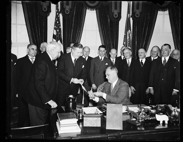 PRESIDENT RECEIVES PAN AMERICAN AWARD. SPRUILLE BRANDEN, MEMBER OF THE COUNCIL OF THE PAN AMERICAN SOCIETY, MAKES THE PRESENTATION OF THE SOCIETY'S AWARD TO PRESIDENT ROOSEVELT. THE AWARD WAS MADE FOR THE PRESIDENT'S 'GOOD NEIGHBOR' POLICY PROMOTING FRIENDSHIP BETWEEN THE NATIONS OF NORTH AND SOUTH AMERICA