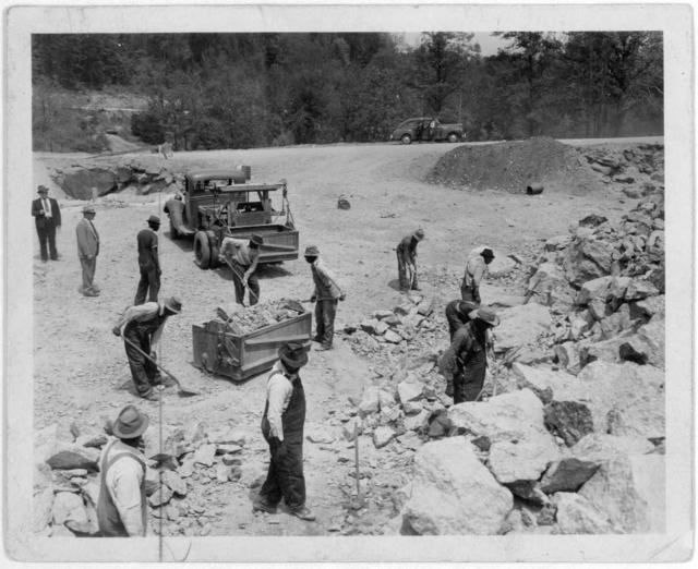 [Prisoners breaking up rocks at a prison camp or road construction site]