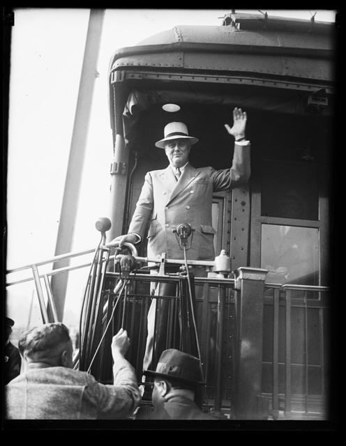 ROOSEVELT BACK FROM VACATION. RETURNING FROM HIS SUMMER WHITE HOUSE AT HYDE PARK, PRESIDENT ROOSEVELT IS CAPABLE OF SMILING DESPITE THE JUMBLED CONDITION OF HIS 'HOUSE OF LETTERS': NRA, AAA, ETC.