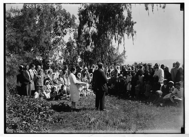 Scots Mission Hospital, Tiberias. Morning service to gathering of out-patients with Rev. Abdullah beside Miss Elsie reading Braille.