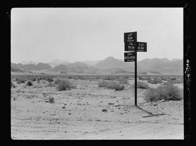 The Araba (Southern end of the great Jordan rift). Negeb el-Shurk. Akaba (Elath). Gulf of Akaba and el-Kuntilla. Araba. Traffic sign near Ibn Saoud boundary, indicating direction to Wadi Rum, Medawera, Ma'an & Akaba