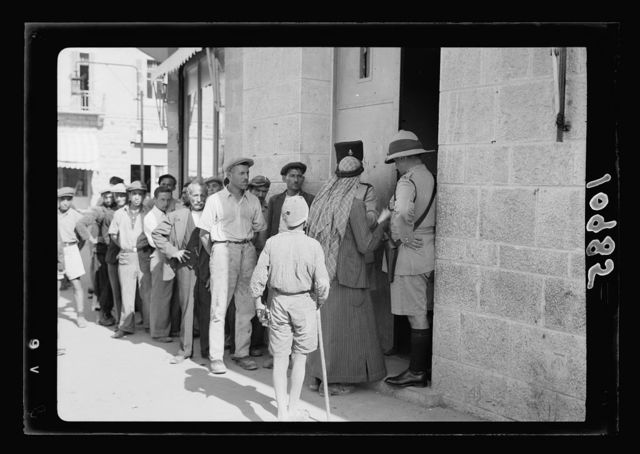 Volunteer queue outside government offices, waiting to register, mostly Jews