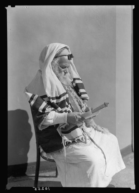 Yemenite Rabbi Avram arrayed for prayer, reading scroll, seated
