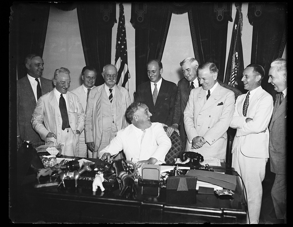 A FUNNY BUSINESS. THE BUSINESS OF GETTING THE PRESIDENTIAL SIGNATURE ON THE ADMINISTRATION'S BANKING BILL TOOK ON A JOCULAR TONE AS PRESIDENT ROOSEVELT, SEATED, JOKES WITH REP. HENRY STEAGALL, (D-AL), WHO HANDLED THE HEARINGS IN HIS HOUSE BANKING AND CURRENCY COMMITTEE. FROM THE LEFT: SEN. CARTER GLASS; COMPTROLLER OF CURRENCY J.F.T. O'CONNOR; SEN. DUNCAN U. FLETCHER (D-FL); SECRETARY HENRY MORGENTHAU; JESSE JONES, CHAIRMAN OF RFC; REP. STEAGALL; AND GOV. MARRINER ECCLES OF THE FEDERAL RESERVE BOARD