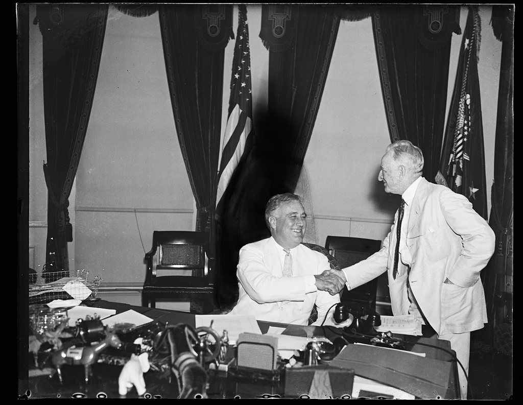 A LITTLE HATCHET BURIAL. PRESIDENT ROOSEVELT, SEATED, GREETS SEN. CARTER GLASS (D-VA) QUITE WARMLY AS SENATORS AND SUCH GATHER AT THE WHITE HOUSE TO WATCH THE PRESIDENT SIGN THE ADMINISTRATION BANKING BILL. SEN. DUNCAN U. FLETCHER (D-FL) STANDS BEHIND PRESIDENT ROOSEVELT. THE LETTERS WERE WRITTEN BY GOVERNOR OF THE SEVEN STATES CROSSED BY THE RIDERS FROM CALIFORNIA TO ST. JOSEPH, MO. SEN. WILLIAM H. KING, (D_UT) IS BETWEEN THE PRESIDENT AND THE MAJOR. STEVE EARLY, ONE OF THE WHITE HOUSE SECRETARIES, IS ON THE EXTREME RIGHT