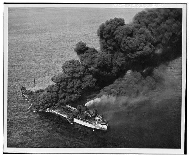 A United States tanker torpedoed by an Axis submarine. Despite a raging fire which sent columns of black, oily smoke billowing into the sky, crew members were able to bring the flames under control and the tanker was towed to port by a United States Naval ship. The tanker is now in an east coast ship yard being repaired and soon will be back in active service aiding the nation against its enemies
