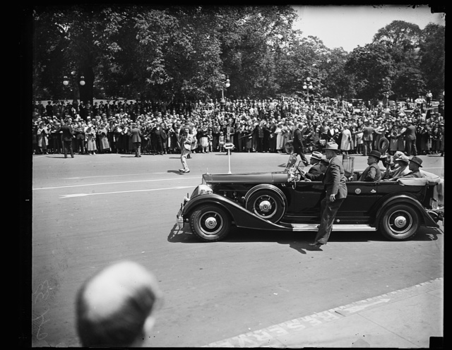 ARRIVES FOR BONUS VETO. PRESIDENT ROOSEVELT WAVES HIS HAT IN SALUTATION TO THE THRONG WHICH GATHERED TO WATCH HIS ARRIVAL AT THE CAPITOL WHERE HE APPEARED BEFORE A JOINT SESSION OF CONGRESS TO DELIVER HIS VETO ON THE PATMAN BONUS BILL. COL. E.W. STARLING, CHIEF OF THE WHITE HOUSE DETAIL OF THE SECRET SERVICE, IS STANDING ON THE RUNNING BOARD OF THE PRESIDENT'S CAR