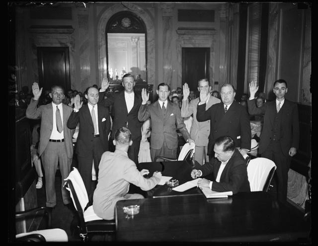 At utility hearing [...] This scene shows a number of witnesses being sworn in at the Senate lobby hearing Monday. Left to right: O.E. Wasser, Controller of A.G.& F.; H.A. Stix, Utility and Financial Accountant of N.Y.; Frank Martin, J.H. Shinn, Pres. of one one of the Utility companies, J.E. Rice Jr., A.G.& F. Treas.; F.S. Burroughs, utility atty; and Warren Partridge, utility witness, 7/29/35