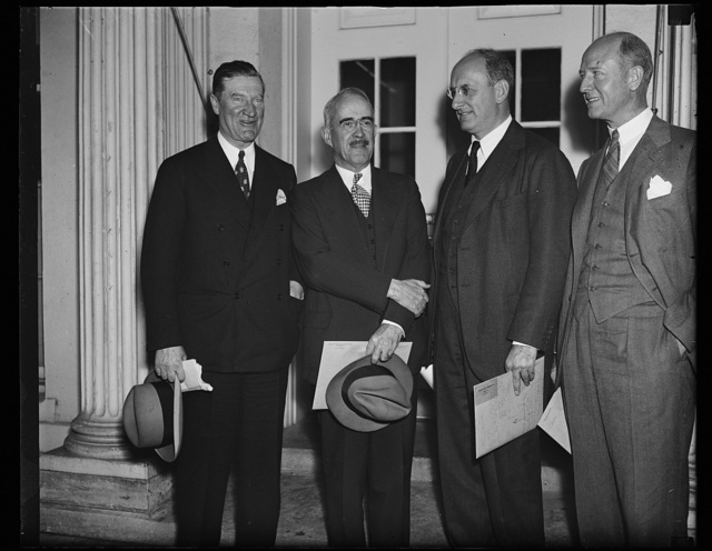 Big talk on little houses. These high officials of the New Deal's housing family photographed as they concluded a conference with President Roosevelt. From the left: Stewart McDonald, head of the [FHA?]; Secretary Henry Morgenthau, Jr., Morris L. Coske, head of Rural Electrification, and Peter Grimm, housing expert working in the Treasury Department. Grimm and his associates from New York are concluding a report on housing conditions east of the Mississippi which is expected to show only from 2 to 4 percent vacancies. His report to the President is expected to have a bearing on the future policy of both Federal Housing, Works Progress Administration, the Rural Electrification program and Rural Resettlement, 10/29/35