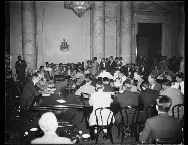 Bombardment starts. On the right of the table, profile showing, is Ewing Y. Mitchell, ousted Assistant Secretary of Commerce, appearing before the Senate Commerce committee to tell his charges of graft in the Commerce Department. On the left are Senators Arthur Vandenberg, R. of Mich., and Royal S. Copeland, D. of N.Y. 6/19/35