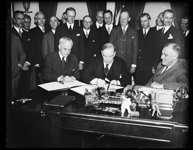 CANADIAN TRADE PACT SIGNED. ADMINISTRATION OFFICIALS RALLIED IN THE EXECUTIVE OFFICE OF THE WHITE HOUSE TO WATCH PRIME MINISTER WILLIAM MacKENZIE KING OF CANADA AND SECRETARY OF STATE CORDELL HULL SIGN THE RECIPROCAL TRADE TREATY DESIGNED TO STRENGTHEN FRIENDSHIP AND ECONOMIC RELATIONS BETWEEN UNITED STATES AND CANADA. PRESIDENT ROOSEVELT, RIGHT, SMILINGLY WATCHES THE APPLICATION OF BINDING SIGNATURES. SECRETARY HULL IS LEFT, AND MacKENZIE KING CENTER. CABINET OFFICERS AND OFFICIALS ARE IN THE BACKGROUND