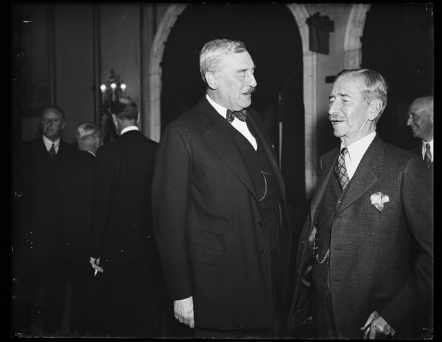 Champion mustaches. Sir Ronald Lindsay, left, Ambassador from England, and Secretary Claude Swanson sport the most outstanding mustaches in official Washington. It is not often that an opportunity for comparison occurs. This occasion was the luncheon given by the Secretary for the visiting Vice Admiral Sir Matthew R. Best of the Royal Navy. 11/1/35