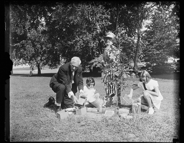 """Constitution oak planted. Kiwanis International plants a """"Constitution Oak"""" on the mall in Washington, D.C., as part of elaborate Constitution Day exercises. Soil from the graves of the farmers of the Constitution and water from the fountains of the 48 state Capitols and the United States were used in this ceremony. From the left: Edwin F. Hill, representing the Kiwanis; Margaret P. Hunter, Robert H. Edmunds, and Elizabeth Hall, 9/17/35"""