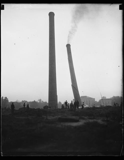 Don't want smokestacks, Wash. D.C. These two 150-foot tall brick smokestacks on the mall in Washington, D.C. were considered an eye sore and ordered demolished. This picture shows one toppling. The other fell shortly thereafter. They first were erected when a central heating plant occupied the site, 9/17/35