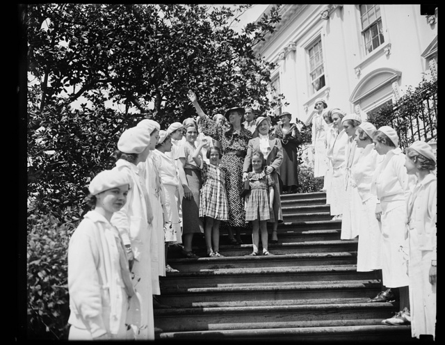 FIRST LADY GREETS GUESTS. MRS. FRANKLIN D. ROOSEVELT GREETS THE THOUSANDS OF CHILDREN CROWDING THE LAWN OF THE WHITE HOUSE IN THE ANNUAL EASTER EGG ROLLING PARTY. FROM THE LEFT: MRS. J. HALL ROOSEVELT OF DETROIT; HER DAUGHTER DIANA; THE FIRST LADY; AMY ROOSEVELT, SISTER OF DIANA; AND MAYRIS CHANEY OF NEW YORK CITY