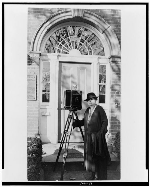 [Frances Benjamin Johnston, full-length portrait, standing in front of door, with camera, facing slightly left]