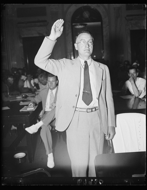 """From headquarters. U.E. Beach, Ithaca, N.Y. Official of the A.G. & E. called Friday before the Senate lobby investigation to testify as to the orders he gave for destroying records of """"directory telegrams."""" He was called from his Ithaca headquarters when testimony of his underlings involved him. Here he is being sworn in. 7/19/35"""