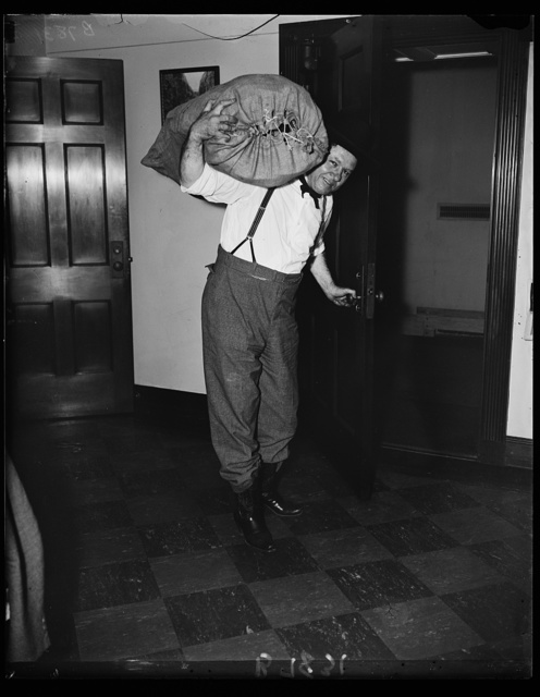 Hooey ... Here's one congressman packing up. There seems to be no hooey about the report that the prankish Rep. of Okla, Percy L. Gassaway is going to leave congress to the Mercies of Senator Huey Long and is going back to Coalgate, Okl. to spend the rest of the year with his Democratic constituents. Here Rep. Gassaway is seen packing up his cowboy regalia in the house office bldg Monday. 7/22/35