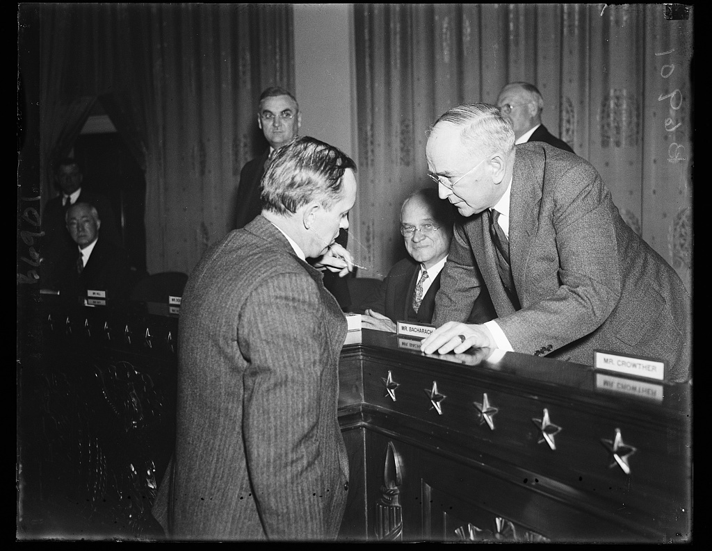 Hopkins gives testimony. Harry Hopkins of FERA, left, is cross examined by Rep. Roy O. Woodruff, R. of Mich. when the FERA Administrator appeared to support the Administration's Social Security program which is being examined by the Ways and Means Committee of the House. 1/23/35