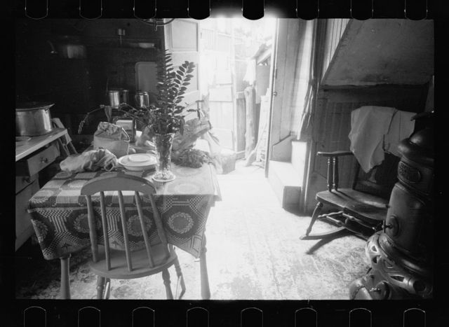 Hovel home of two Negro families, Washington, D.C. Near ice chest is the privy, although unseen in this picture. A recent relief visit accounts for the food on the table