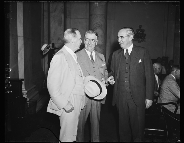 In self-defense. Secretary of Commerce Daniel C. Roper, left, appears at the Senate commerce committee, to defend his department against charges of graft and corruption hurled by Ewing Y. Mitchell, ousted assistant Sen. Royal B. Copeland, D. of N.Y., center , is chairman of the committee, and Sen. Arthur H. Vandenberg, R. of Mich., right, is taking an active part in the proceedings. 6/19/35