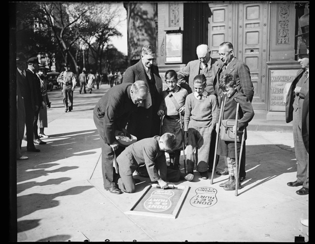 In traffic safety drive. These children, students at a crippled children's school, are painting giant footprints at dangerous intersections as warnings to pedestrians. Standing, from the left: Wm. A. Van Duzer, Traffic Director; Inspector L.I.H. Edwards, Assistant Director M.O. Edlridge, and Harold Marsh, President of the Washington Kiwanis Club. Seated: LeRoy Padgett, James Cline, Belmont Poole and Jimmy Smith, on crutches, all students, 10/4/35