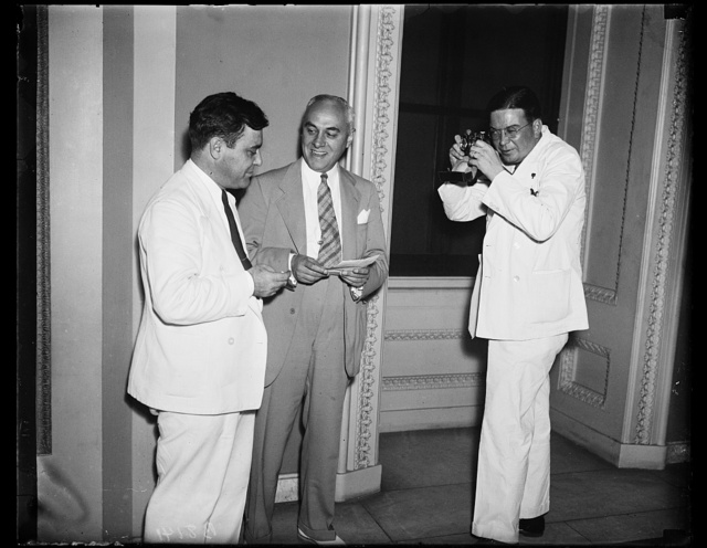 """It must be the heat, Wash. D.C. Congressmen have been blinking into cameras since the opening of the session, Jan. 3, and now they have started """"shooting"""" each other. This photograph shows, from the left, Rep. Gerald Boileau, Progressive of Wis.; Rep. Louis C. Rabaut, D. of Mich., and Rep. Paul Kvale, Farm-Labor of Minn. The Congressman with the candid camera was industriously banging away on the floor of the house when he was informed that he was breaking the rules. So he went outside, as the session was almost over anyway, 8/23/35"""