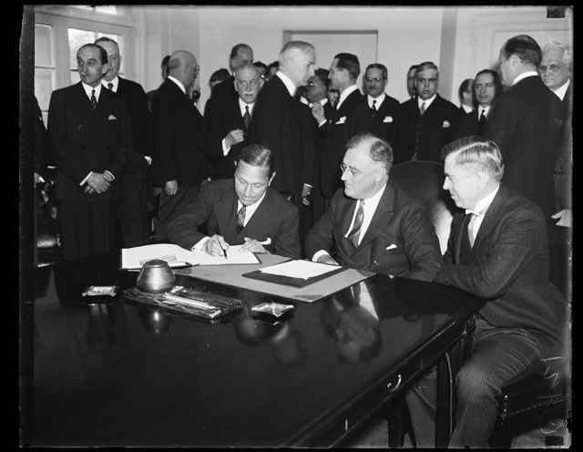 KING'S X TREATY. REPRESENTATIVES OF 20 GOVERNMENTS CONCUR WHILE THE KING'S X TREATY IS SIGNED TO OUTLAW DESTRUCTION OF SCIENTIFIC, ARTISTIC AND HISTORIC MONUMENT IN TIME OF WAR. FROM THE LEFT: AMBASSADOR SENOR DON FELIPE A. ESPIL OF SPAIN; PRESIDENT ROOSEVELT; AND SECRETARY HENRY WALLACE OF THE AGRICULTURE DEPARTMENT
