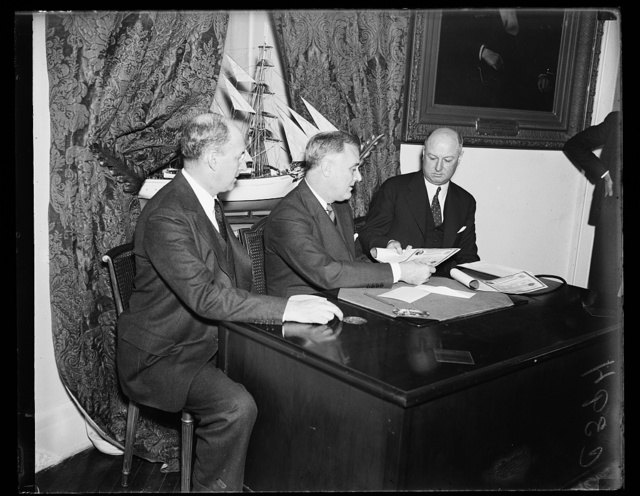 LOOKS LIKE A DEAL. PMG JAMES FARLEY, RIGHT, SEEMS PLEASED WITH THE PROSPECT OF MAKING HIS FIRST SALE OF 'BABY BONDS.' PRESIDENT ROOSEVELT, CENTER, FINALLY BOUGHT HALF A DOZEN, ONE FOR EACH OF HIS FIVE GRANDCHILDREN AND ONE FOR HIMSELF. SECRETARY HENRY MORGENTHAU, JR., WHOSE DEPARTMENT SELLS THE BONDS THROUGH POST OFFICES, WATCHES PROCEEDINGS