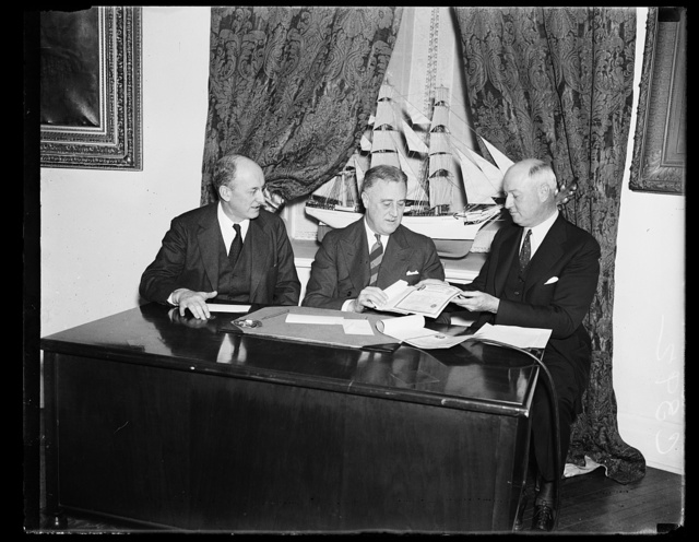 LOOKS LIKE A DEAL. PMG JAMES FARLEY, RIGHT, SEEMS PLEASED WITH THE PROSPECT OF MAKING HIS FIRST SALE OF 'BABY BONDS.' PRESIDENT ROOSEVELT, CENTER, FINALLY BOUGHT HALF A DOZEN, ONE FOR EACH OF HIS FIVE GRANDCHILDREN AND ONE FOR HIMSELF. SECRETARY HENRY DREN AND ONE FOR HIMSELF. SECRETARY HENRY MORGENTHAU, JR., WHOSE DEPARTMENT SELLS THE BONDS THROUGH POSTOFFICES, WATCHES PROCEEDINGS