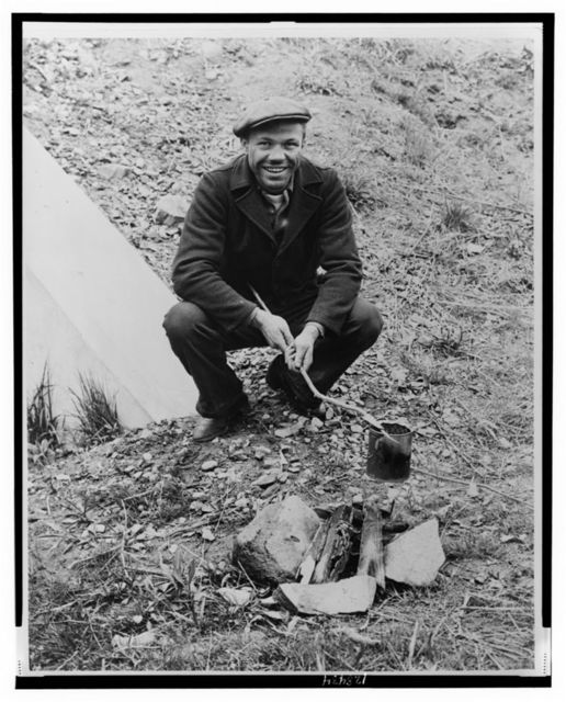 [Lou Ambers cooking over a campfire, using a tin can on a stick) / Staff photo by Alan Fisher