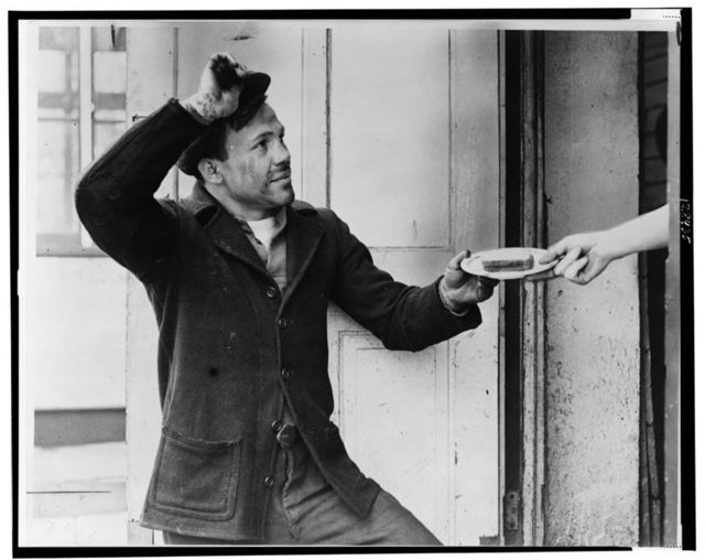 [Lou Ambers tips his hat as he accepts a sandwich from a hand reaching out of a doorway] / Staff photo by Alan Fisher.
