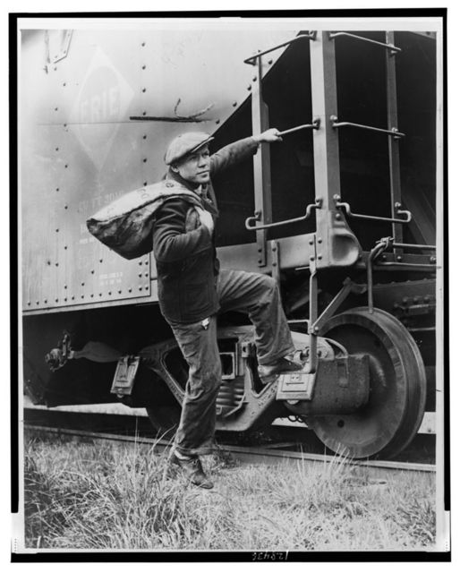 [Lou Ambers with a large bag over his shoulder, mounting the ladder of a train car] / Staff photo by Alan Fisher.