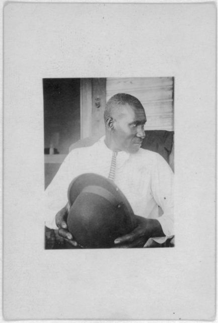 [Man seated, facing right, holding hat, Eatonville, Fla., taken during the Lomax, Hurston, Barnicle 1935 expedition to Georgia, Florida and the Bahamas]