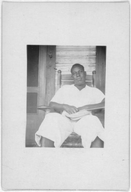 [Man seated in rocking chair, facing forward, Eatonville, Fla.,  taken during the Lomax, Hurston, Barnicle 1935 expedition to Georgia, Florida and the Bahamas]