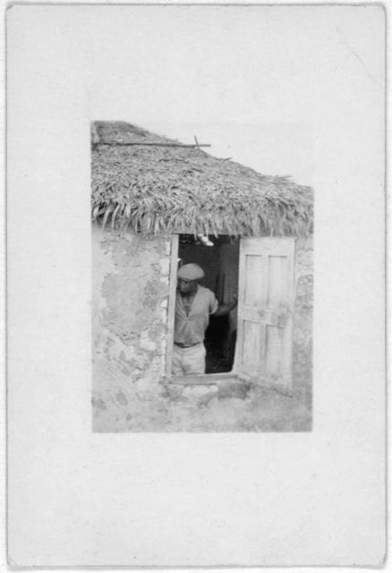 [Man standing at door of house, looking out, possibly from the visit by Alan Lomax and Mary Elizabeth Barnicle to Cat Island in the Bahamas]