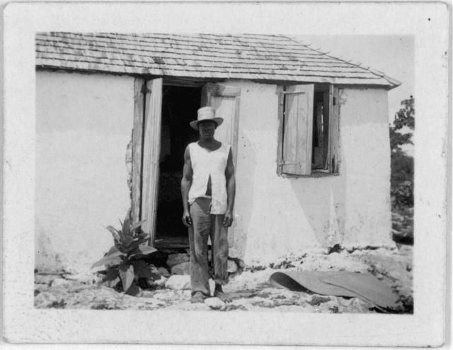 [Man standing in front of house, possibly from the visit by Alan Lomax and Mary Elizabeth Barnicle to Andros Island in the Bahamas]