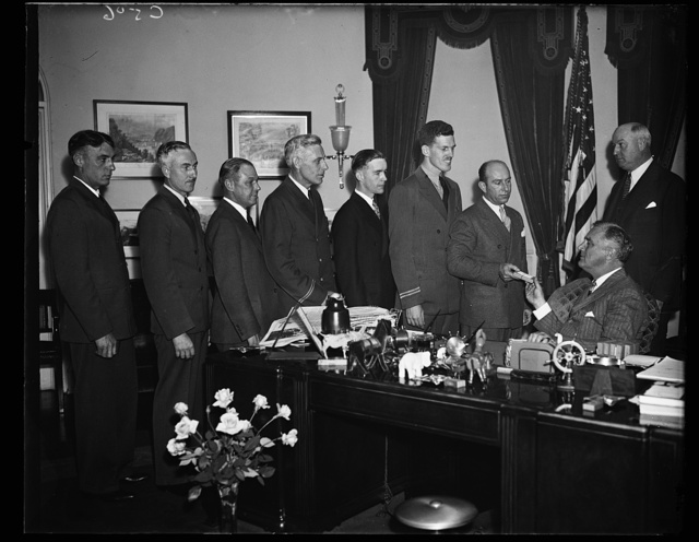 MEDALS FOR BRAVE FLIERS. PRESIDENT ROOSEVELT AWARDS AIR MAIL FLYER'S MEDALS OF HONOR TO PILOTS PERFORMING ACTS OF HEROISM. FROM THE LEFT: ROY H. WARNER, UNITED AIR LINES; GROVER TYLER, UNITED AIR LINES; LEWIS TURNER, AMERICAN AIRWAYS; WALLINGTON P. McFAIL, AMERICAN AIRWAYS; WALLINGTON P. McFAIL, AMERICAN AIRWAYS; GORDON S. DARNELL, U.S. AIRLINES; JAMES CARMICHAEL, JR, CENTRAL AIR LINES; EDWARD A. BELLAND, TWA; PRESIDENT ROOSEVELT; AND PMG JAMES A FARLEY