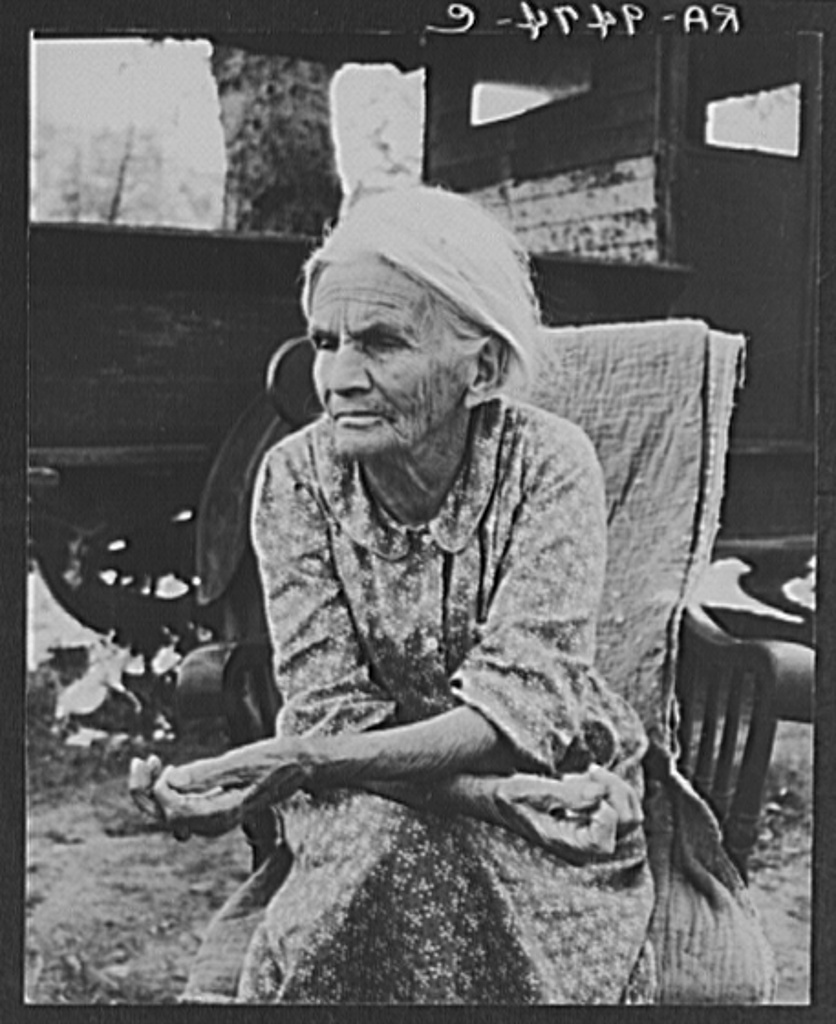 """Mother of family camped near a creek bed, panning for gold. """"Slept in a bed all my life long till now--sleeping on the ground."""" Near Redding, California"""