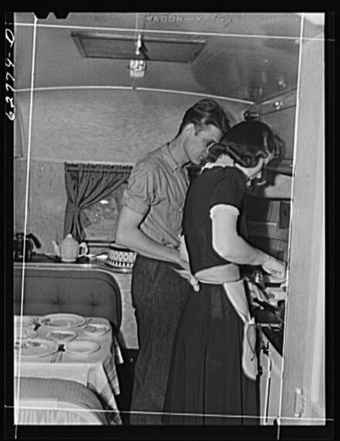 Mr. and Mrs. Jack Cutter preparing noonday meal in kitchen of their trailer home. FSA (Farm Security Administration) camp, Erie, Pennsylvania