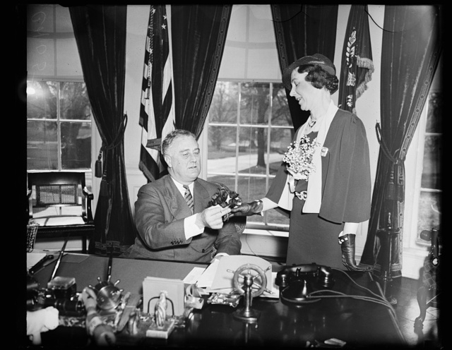 MRS. A.C. CARLSON, NATIONAL PRESIDENT OF THE AMERICAN LEGION AUXILIARY, PRESENTS A VETERAN-MADE POPPY TO PRESIDENT ROOSEVELT. THE ORGANIZATION SELLS POPPIES EACH YEAR TO RAISE MONEY FOR VETERANS SUFFERING FROM WAR INJURIES