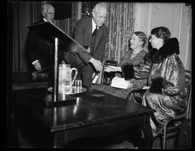 MRS. ROOSEVELT OPENS SLUM CLEARANCE MEETING. MRS. FRANKLIN D. ROOSEVELT IS GREETED BY NORMAN THOMAS AS THE FIRST LADY PREPARES TO OPEN THE NATIONAL PUBLIC HOUSING CONFERENCE AT THE WILLARD HOTEL IN WASHINGTON FRIDAY NIGHT. IN CENTER IS MARY KINGSBURY SIMKHOVITCH, NEW YORK, PRESIDENT OF THE NATIONAL PUBLIC HOUSING CONFERENCE