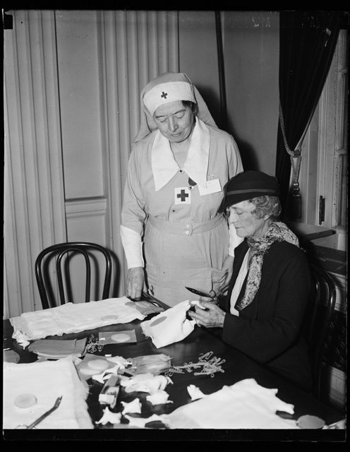 Mrs. Swanson helps Red Cross on bandages. Mrs. Albert T. Niblack, standing, instructs Mrs. Claude Swanson, wife of the Secretary of Navy, in the art of making bandages. Mrs. Niblack is in charge of this work for the American Red Cross in Washington, D.C. The Red Cross has been supplying materials, funds, and assistance to Ethiopia to help care for the wounded from the battlefields where Italian troops are invading their country, 11/5/35
